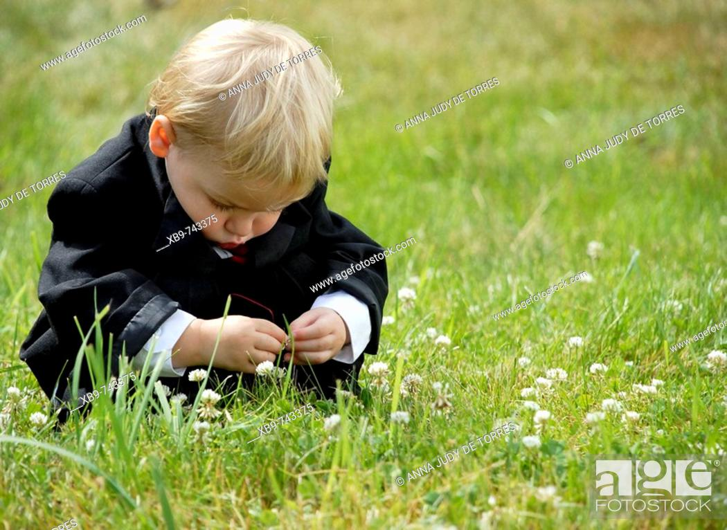 Stock Photo: A little boy squatting in the grass.