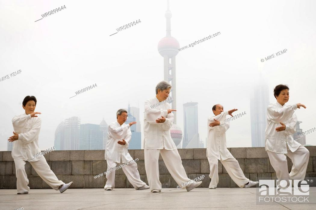 Stock Photo: Group doing tai chi outdoors with city skyline in background.