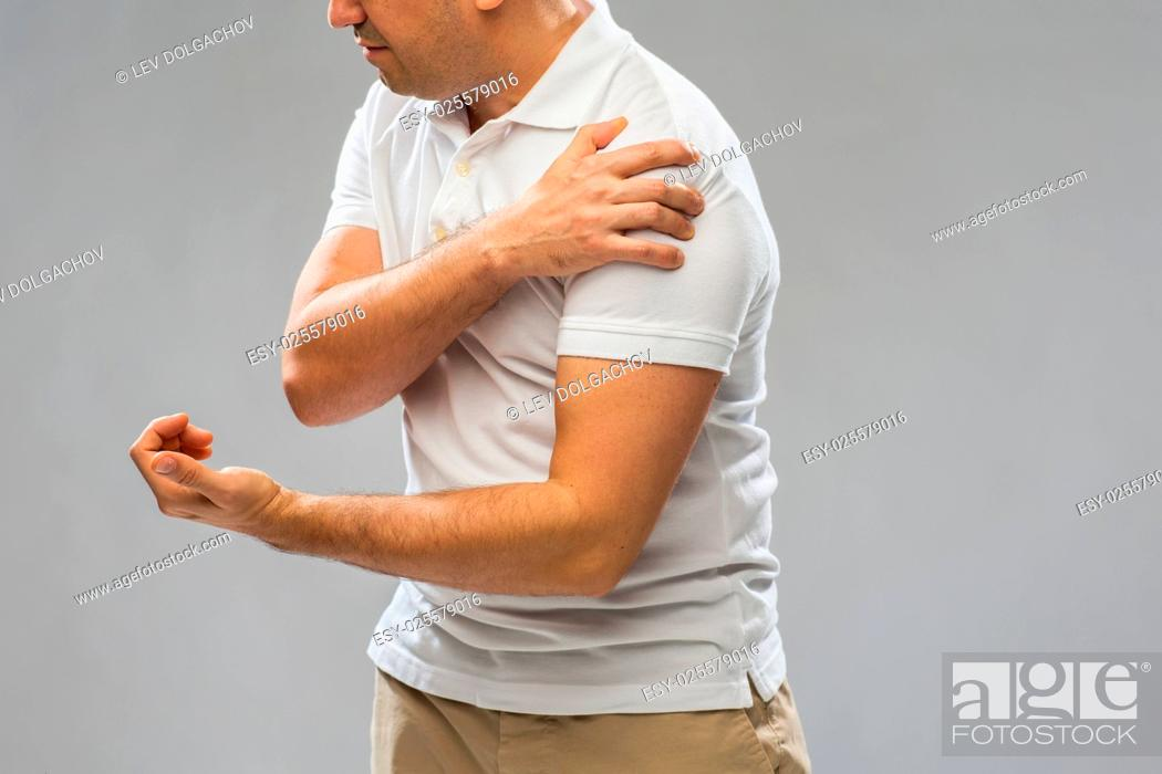 Stock Photo: people, healthcare and problem concept - close up of man suffering from pain in hand over gray background.