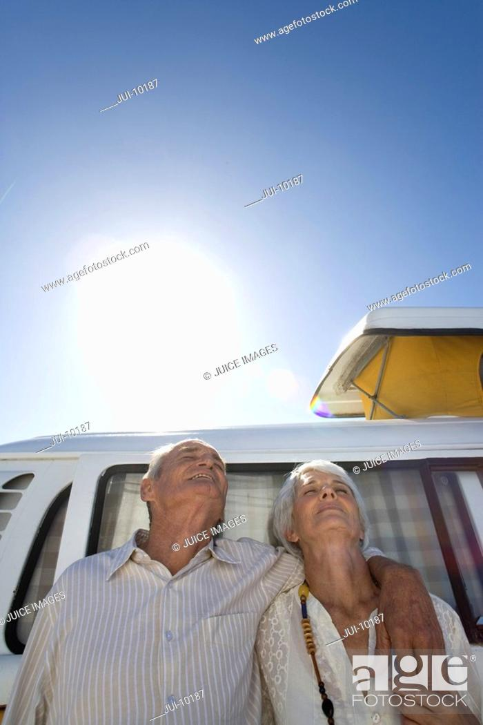 Stock Photo: Senior couple arm in arm against camper van, low angle view.