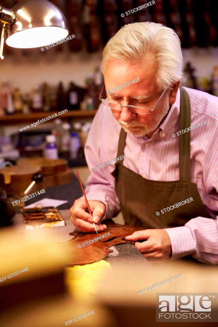 Imagen: Man Restoring Violin In Workshop.