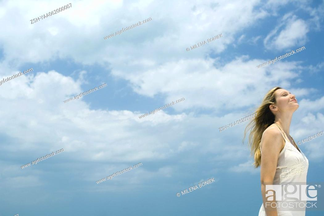 Stock Photo: Young woman standing outdoors with head back, eyes closed, side view, low angle.