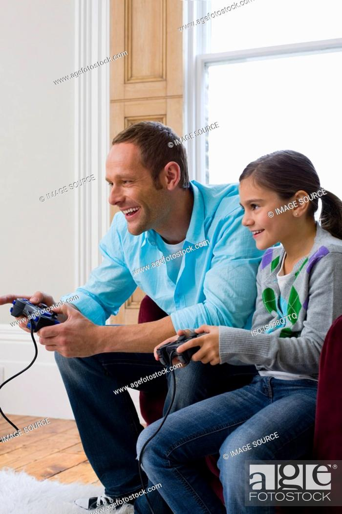 Stock Photo: Father and daughter playing video game.