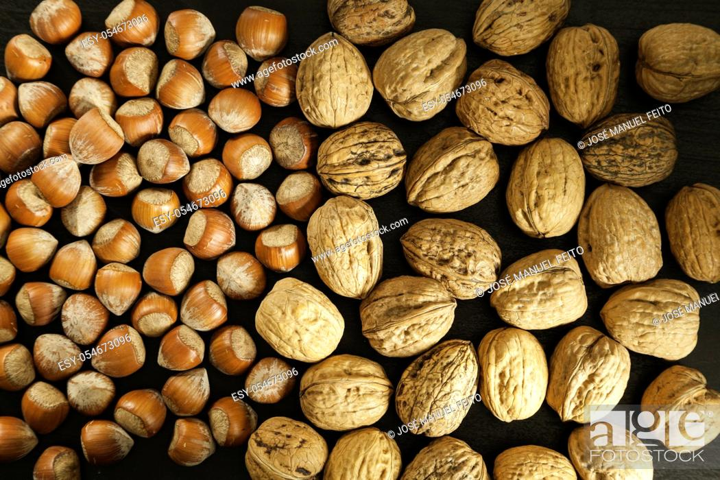 Stock Photo: Hazelnuts and walnuts half and half on dark background top view.