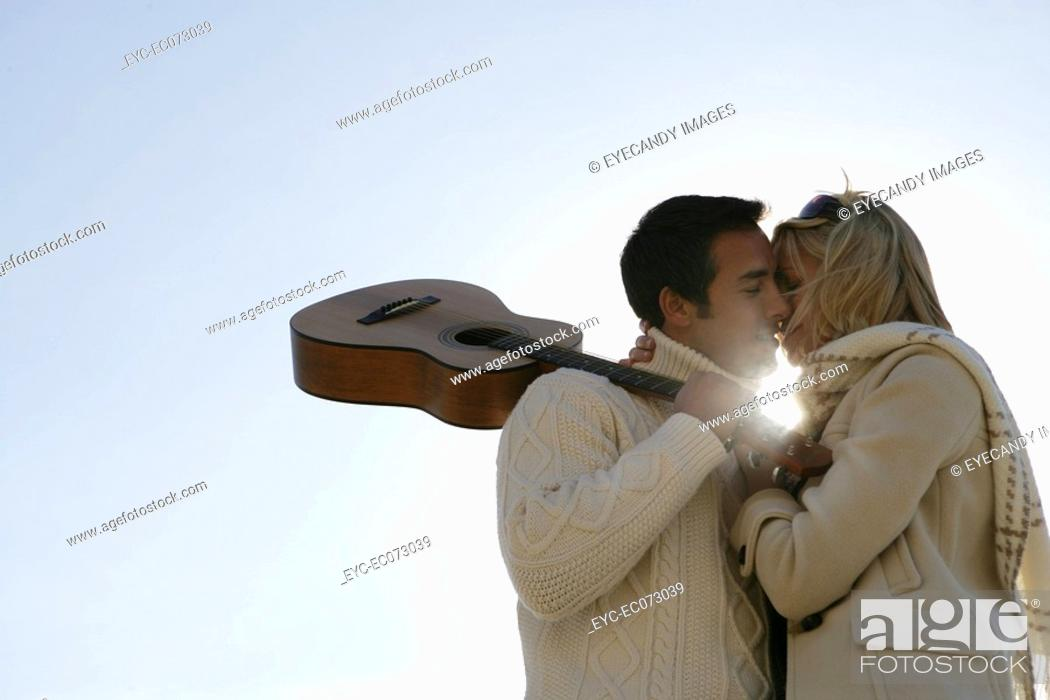 Stock Photo: Young couple with guitar kissing.