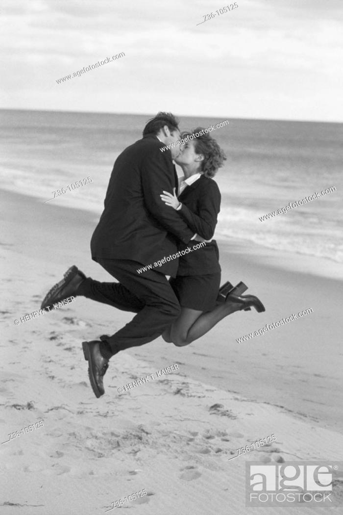 Stock Photo: Businesspeople kissing on beach.