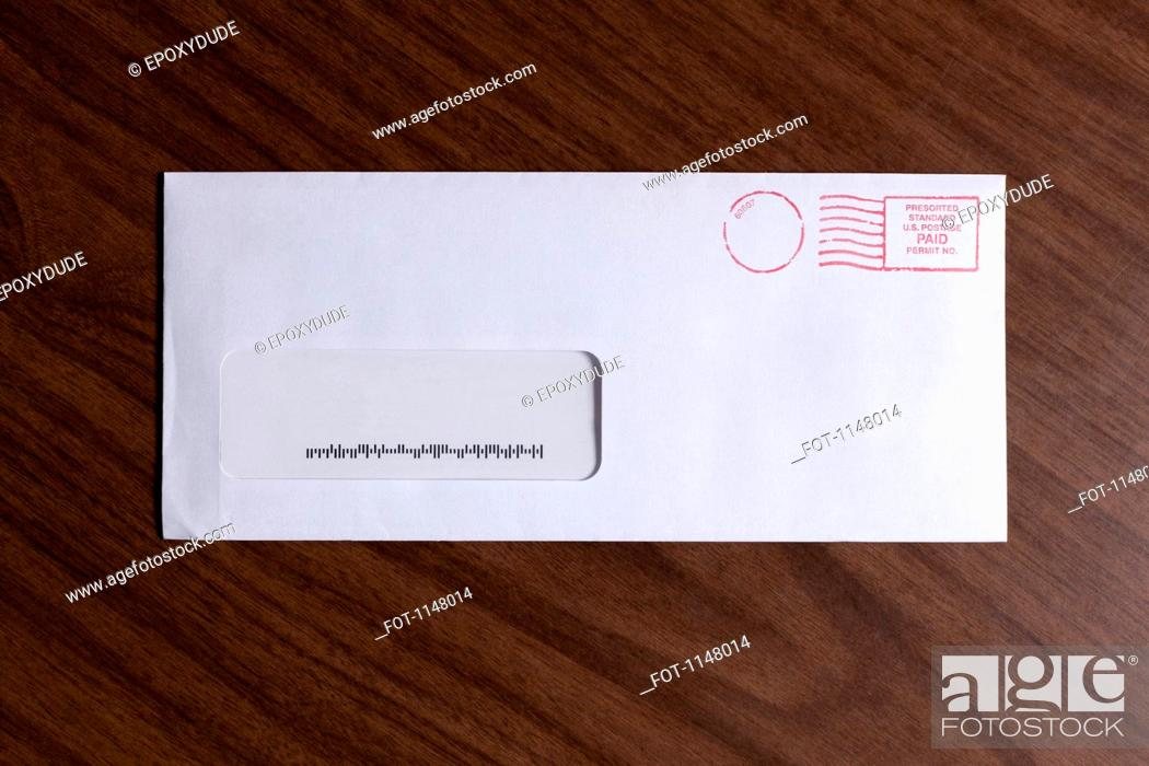 Stock Photo: A window envelope with no address, but a barcode and red ink postage stamp.