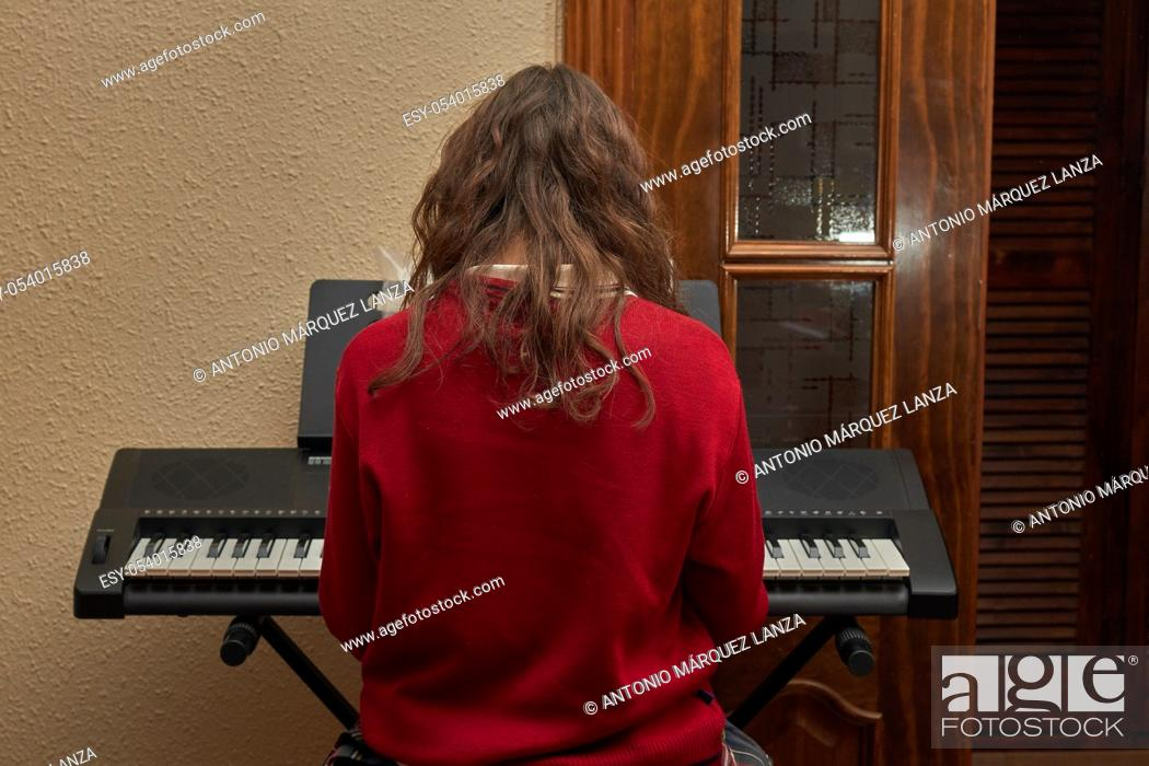 Stock Photo: girl playing piano in her house.