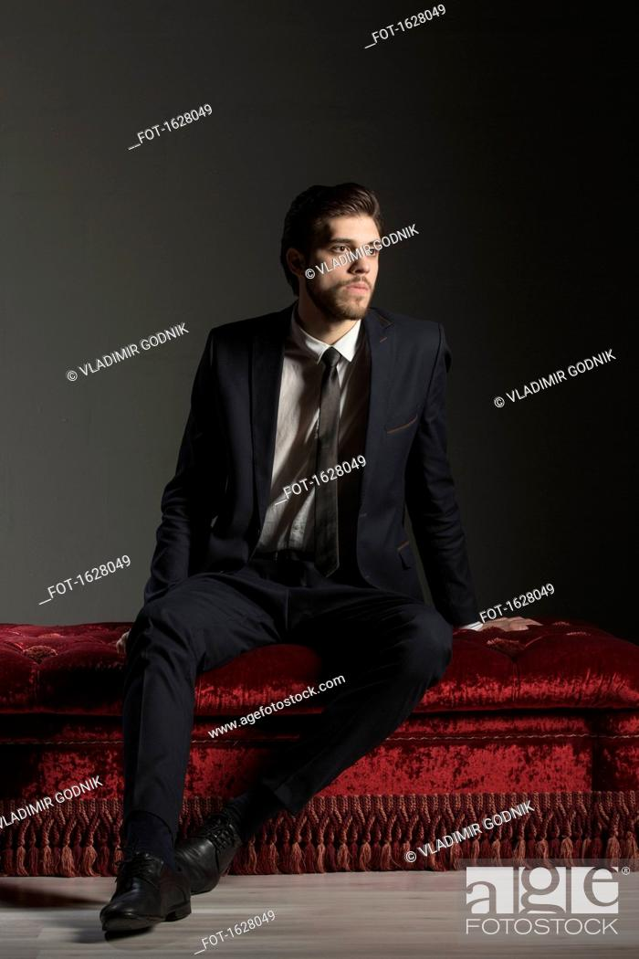 Stock Photo: Full length thoughtful businessman sitting on ottoman against gray background.