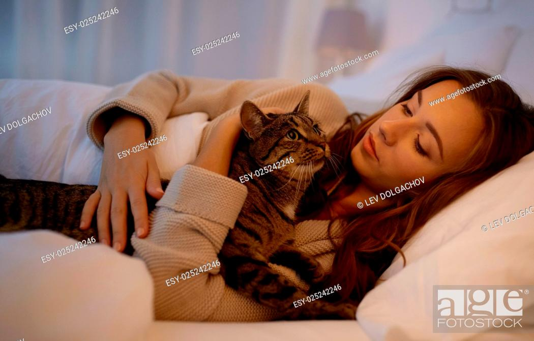 Stock Photo: pets, comfort, rest and people concept - happy young woman with cat lying in bed at home at night.