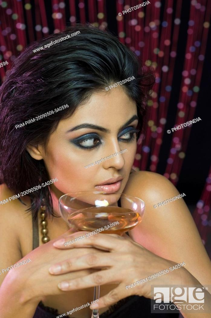 Stock Photo: Woman holding a wine glass in a nightclub.