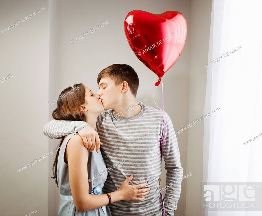 Stock Photo: Couple kissing, holding heart balloon.