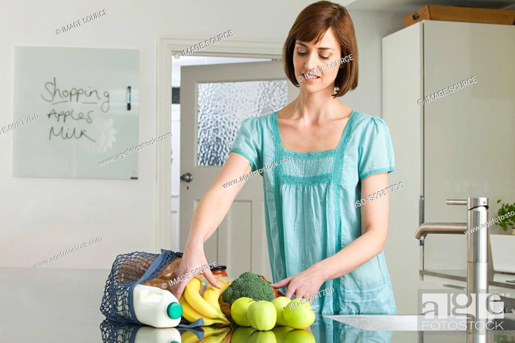 Stock Photo: Woman unpacking groceries.