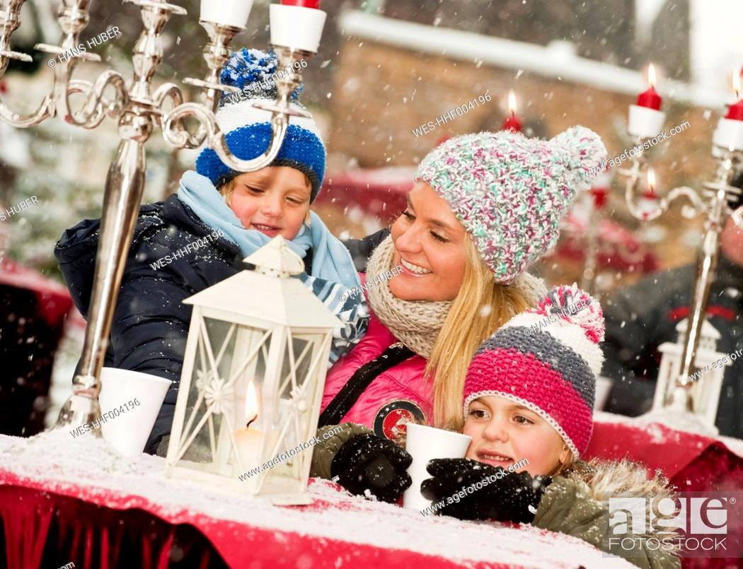 Stock Photo: Austria, Salzburg, Mother with children at christmas market, smiling.