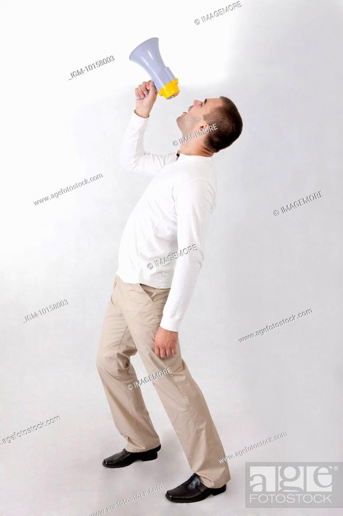 Stock Photo: Young man holding a megaphone and shouting.