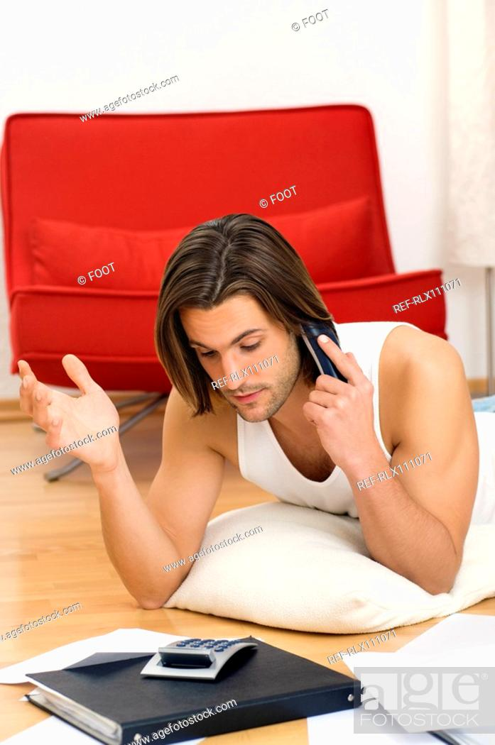 Stock Photo: Man on phone doing home finances.