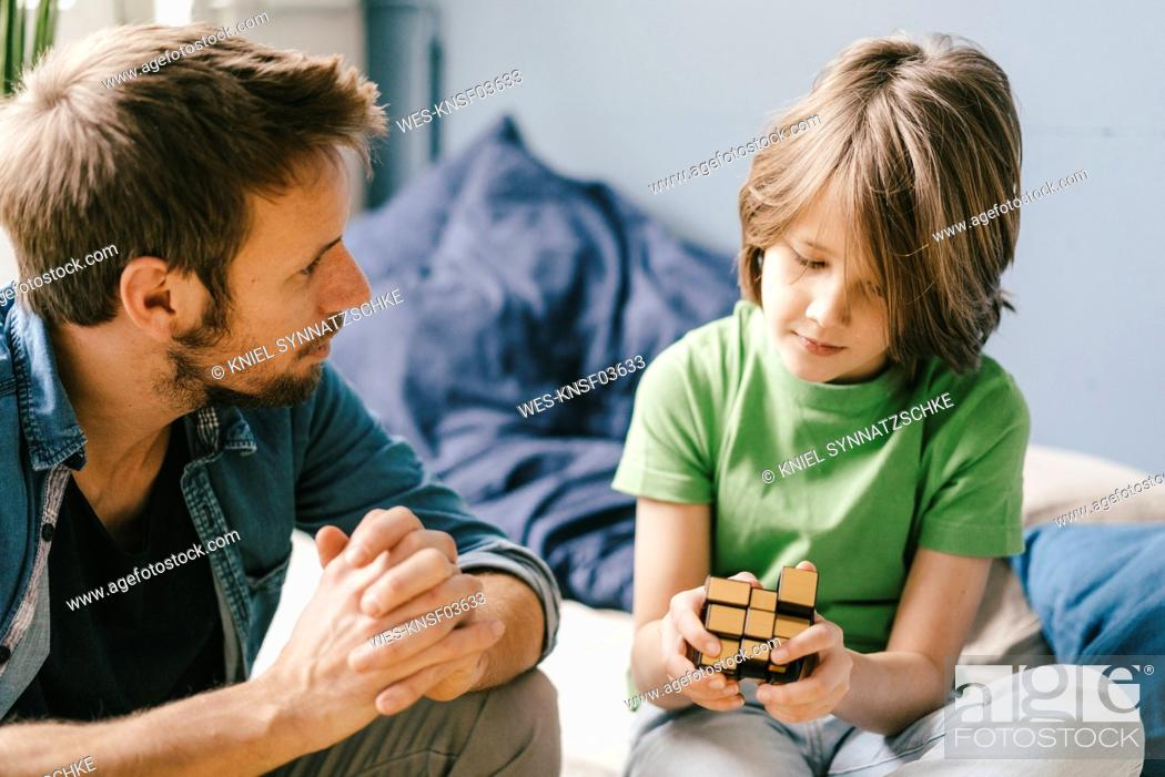 Stock Photo: Father looking at son playing with cube a at home.