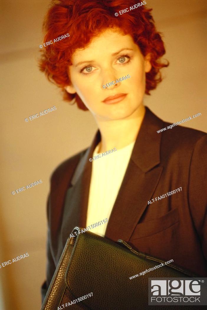 Stock Photo: Businesswoman standing with briefcase underarm, portrait.