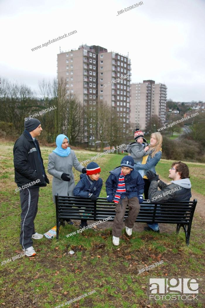 Stock Photo: Families chatting by bench with tower blocks behind.