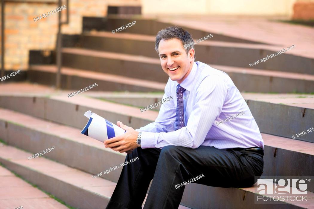 Stock Photo: Caucasian businessman sitting on staircase holding paperwork.
