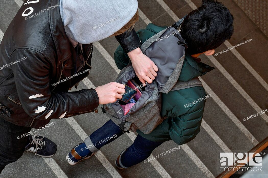 Stock Photo: Diebstahl eines Handys aus Rucksack, Strassenkriminalitaet, gestelltes Foto.