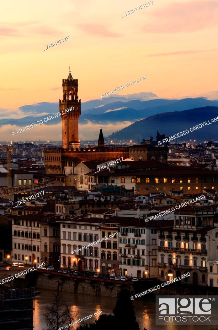 Stock Photo: Palazzo Vecchio, also known as Palazzo della Signoria, with the Arno river in Florence photographed at sunset dusk with clouds over the far hills.