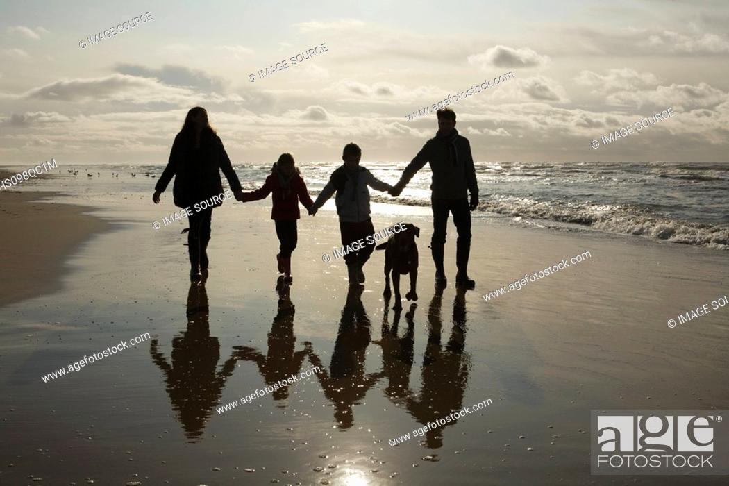 Stock Photo: Family and dog by the sea.