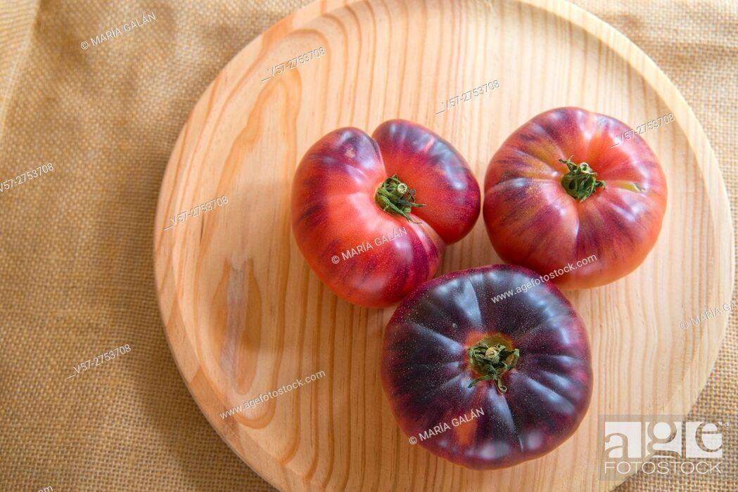 Stock Photo: Three blue sea tomatoes on wooden dish. Still life.