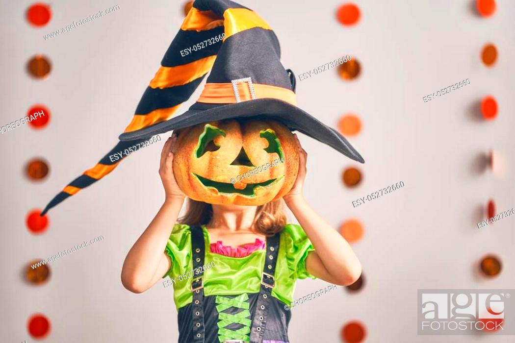 Stock Photo: Happy Halloween! Cute little laughing girl in witch costume with a pumpkin.