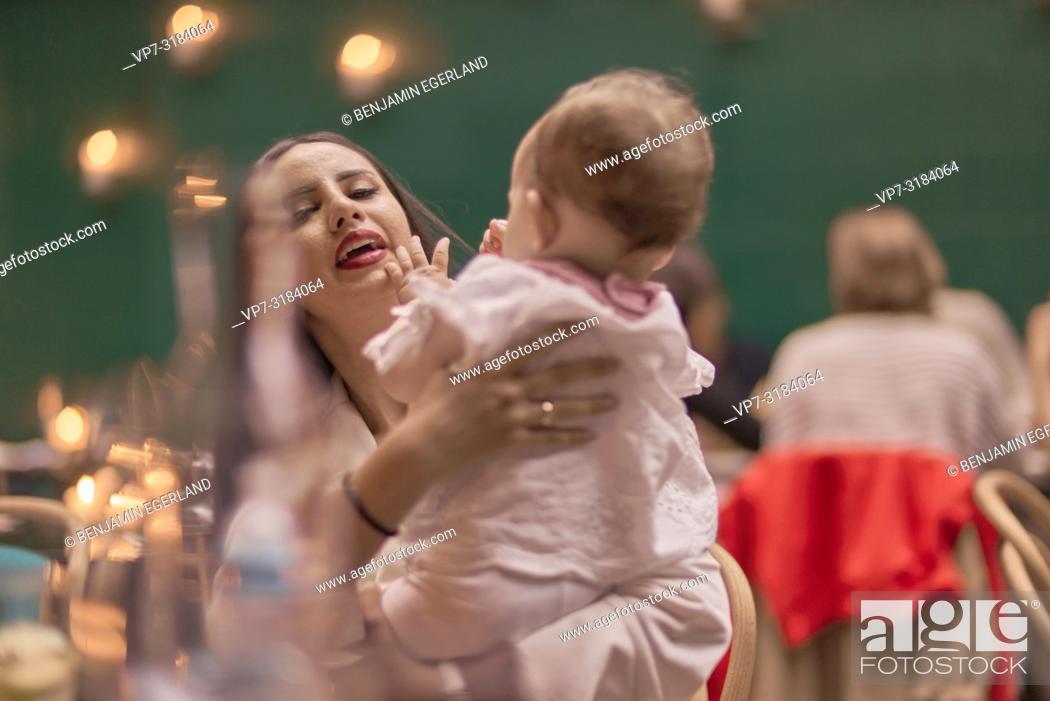 Imagen: mother with baby in restaurant, Vegan Oriental, Kismet, in Munich, Germany.