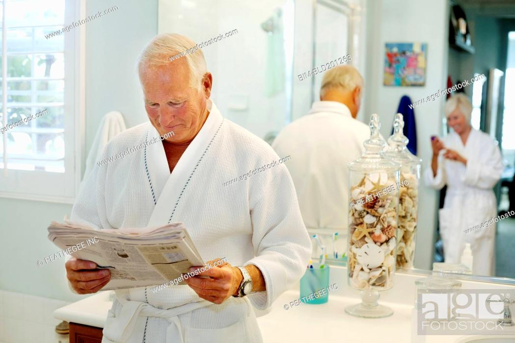 Stock Photo: Caucasian man reading newspaper in bathroom.