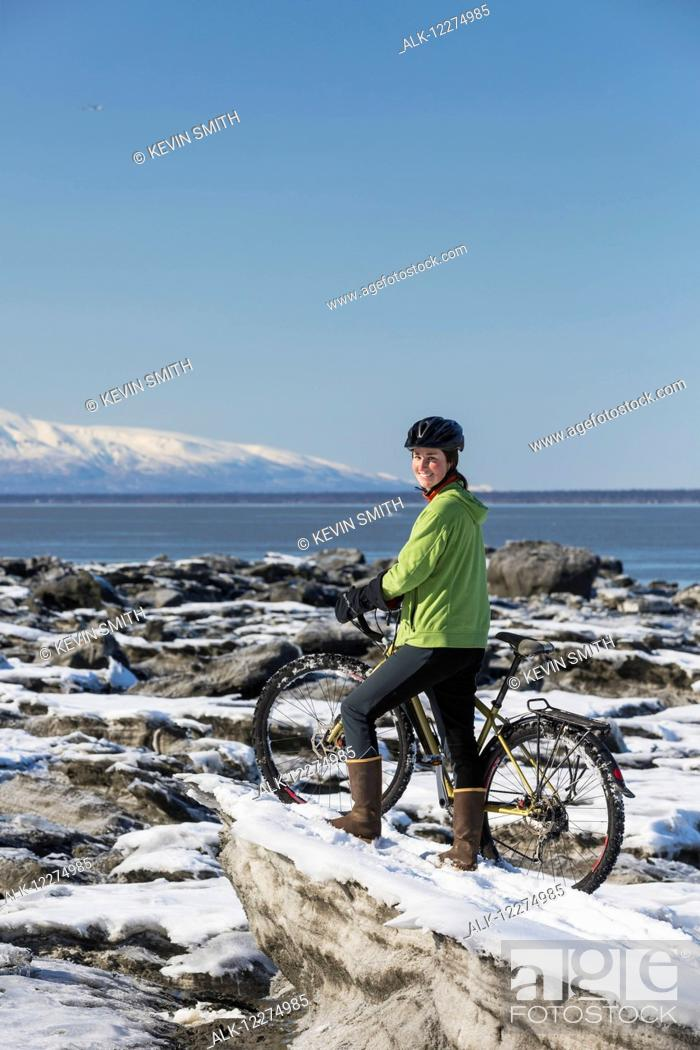 Stock Photo: Young woman with her bicycle stands on frozen ice chunks along the Tony Knowles Coastal Trail, Anchorage, Southcentral Alaska.