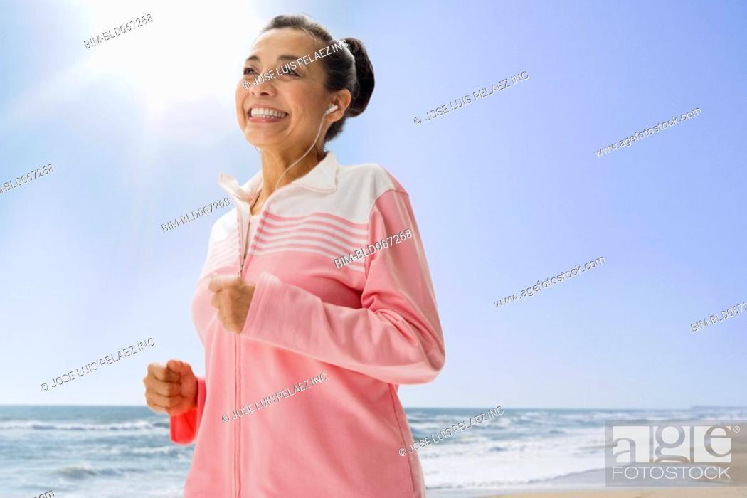 Stock Photo: Hispanic woman jogging on beach.