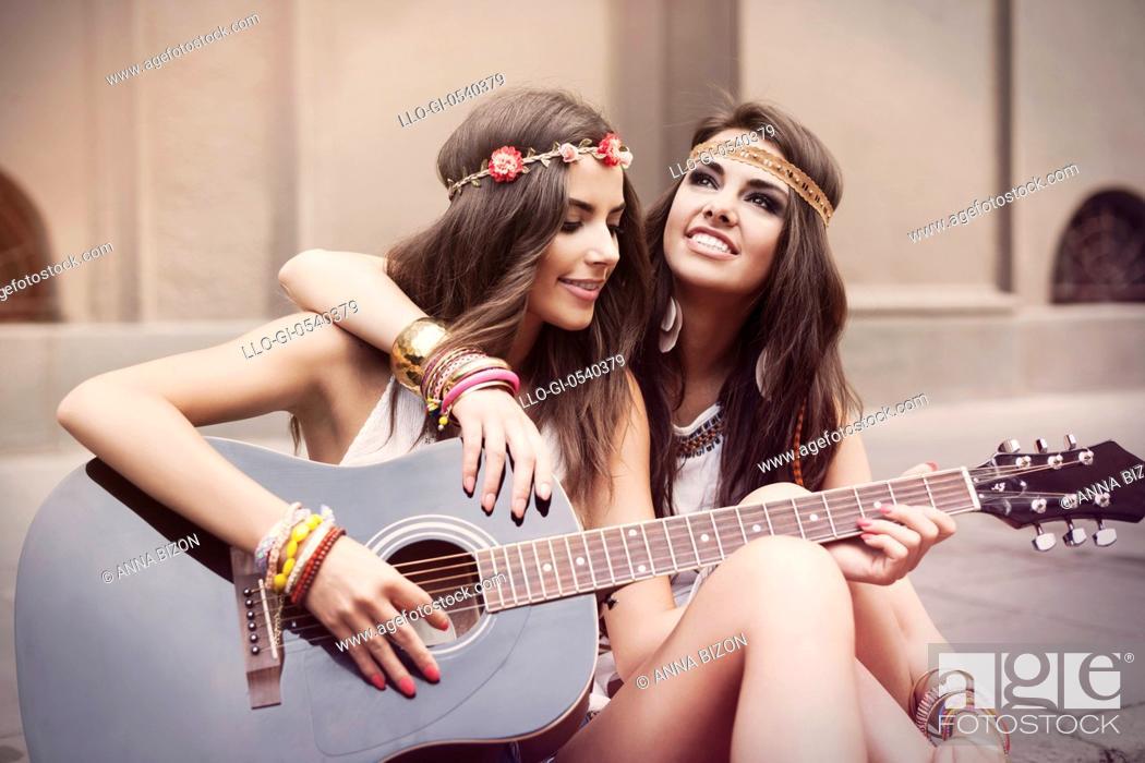 Stock Photo: Beautiful stylish friends playing guitar. Krakow, Poland.