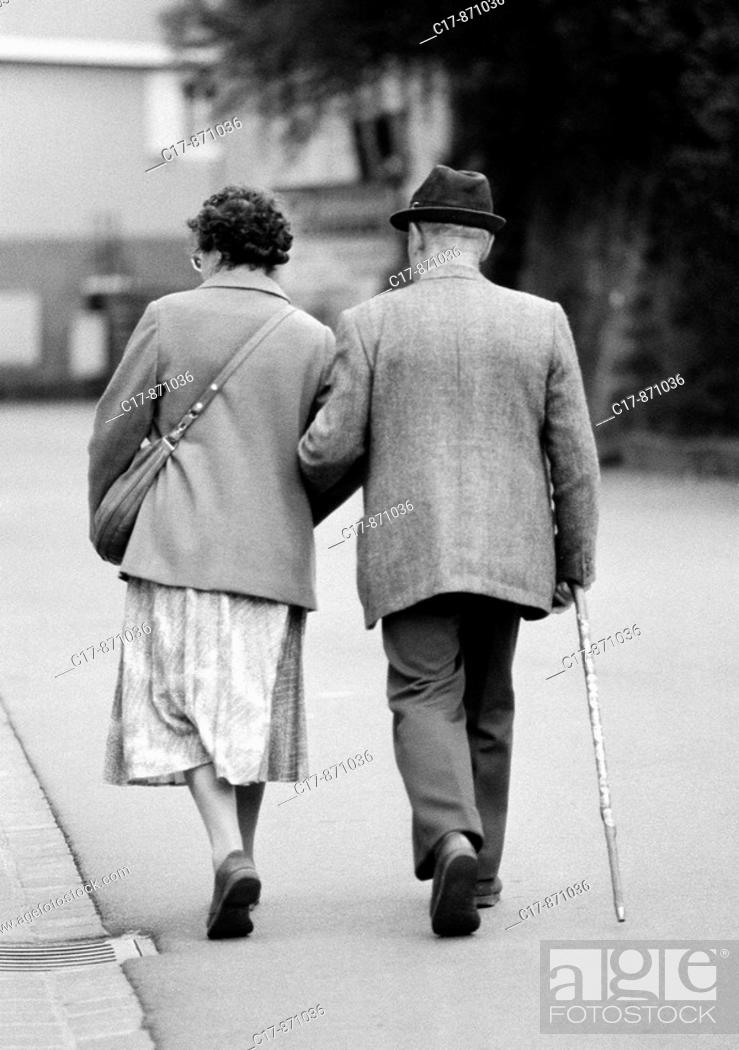 Imagen: Eighties, black and white photo, people, elder people, older couple walking arm in arm, jacket, trousers, skirt, hat, aged 65 to 75 years.