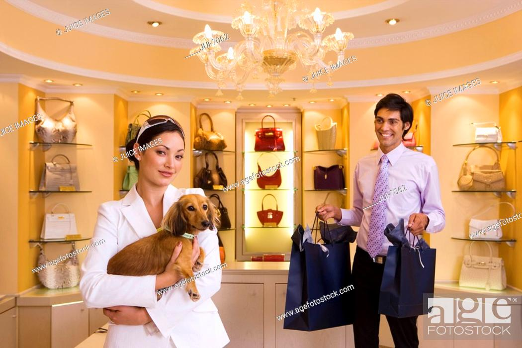 Stock Photo: Young woman shopping with dog in glamorous designer handbag boutique, male shop assistant carrying bags, smiling, portrait.