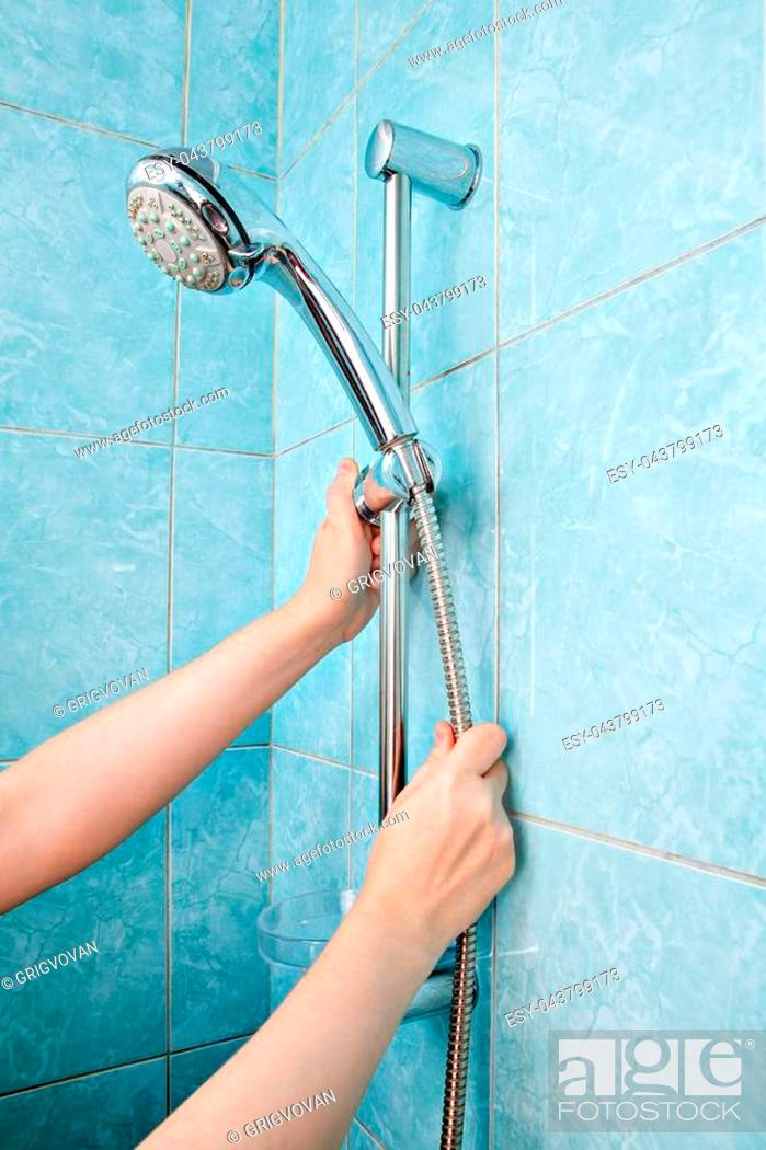 Stock Photo: Replacing the plumbing in the bathroom, close-up human hands installed hose with shower head in height adjustable shower bar slider rail.