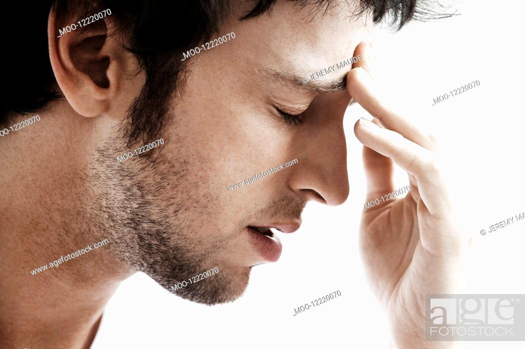 Stock Photo: Man with Headache touching forehead close up.