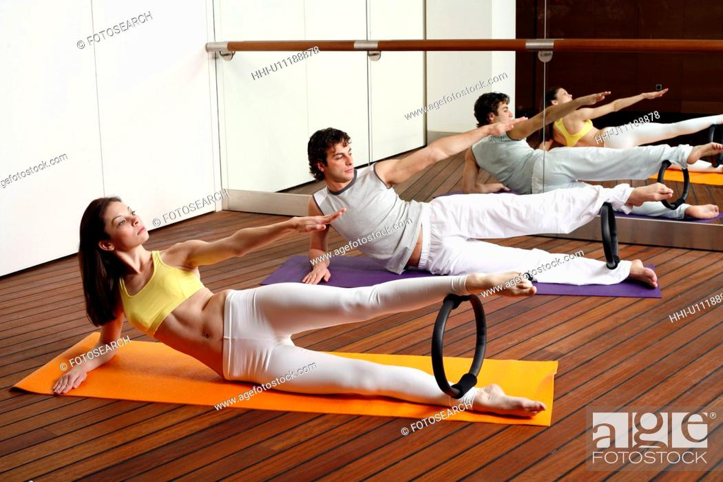 Stock Photo: Young man and woman performing a pilates exercise.