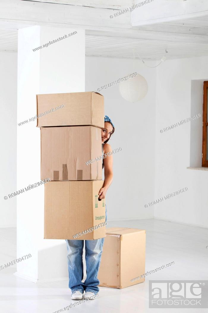 Stock Photo: Young woman carrying cardboard boxes.