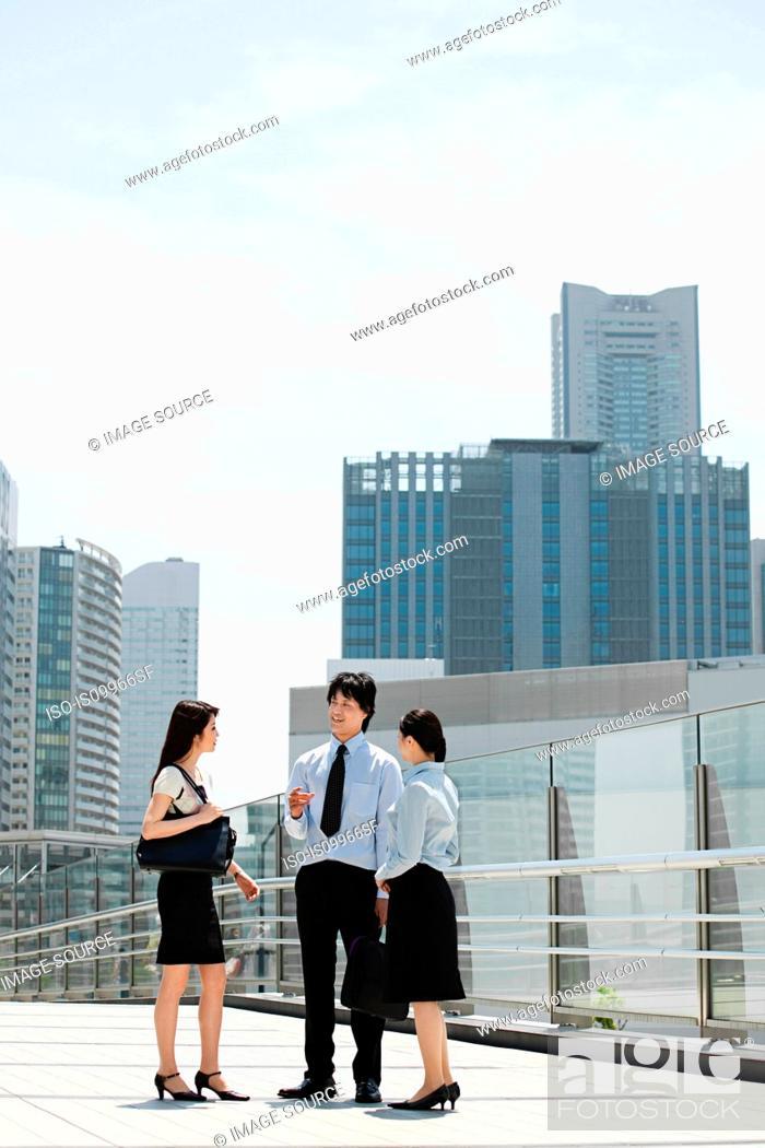 Stock Photo: Businesspeople standing in city scene.