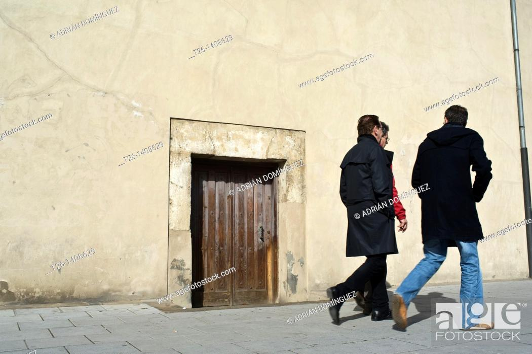 Stock Photo: Group walk close to a little door in the city of León, Spain.