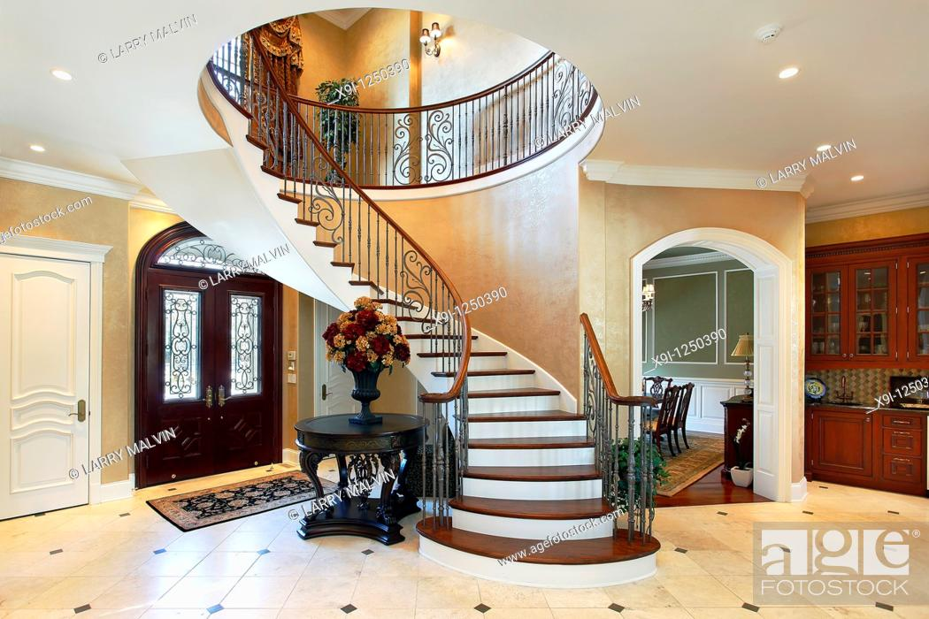 Stock Photo: Foyer in luxury home with circular staircase.