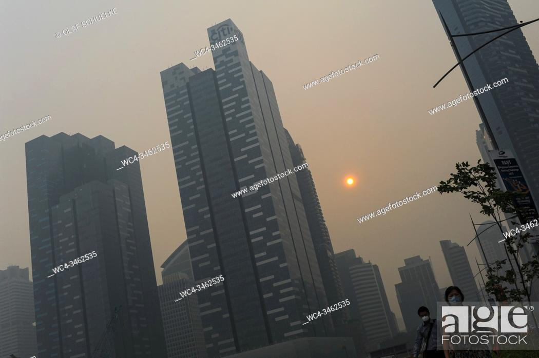 Imagen: Singapore, Republic of Singapore, Asia - People wearing face masks walk through the hazardous haze that shrouds the central business district with its.