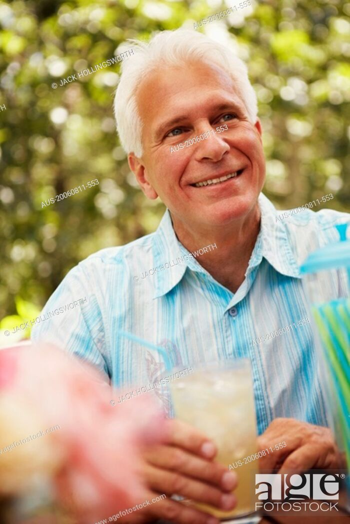 Stock Photo: Close-up of a mature man holding a glass of a juice and smiling.