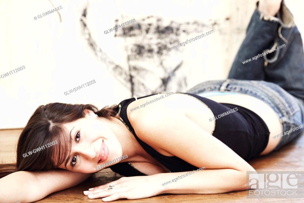 Stock Photo: Portrait of a young woman lying on the floor.