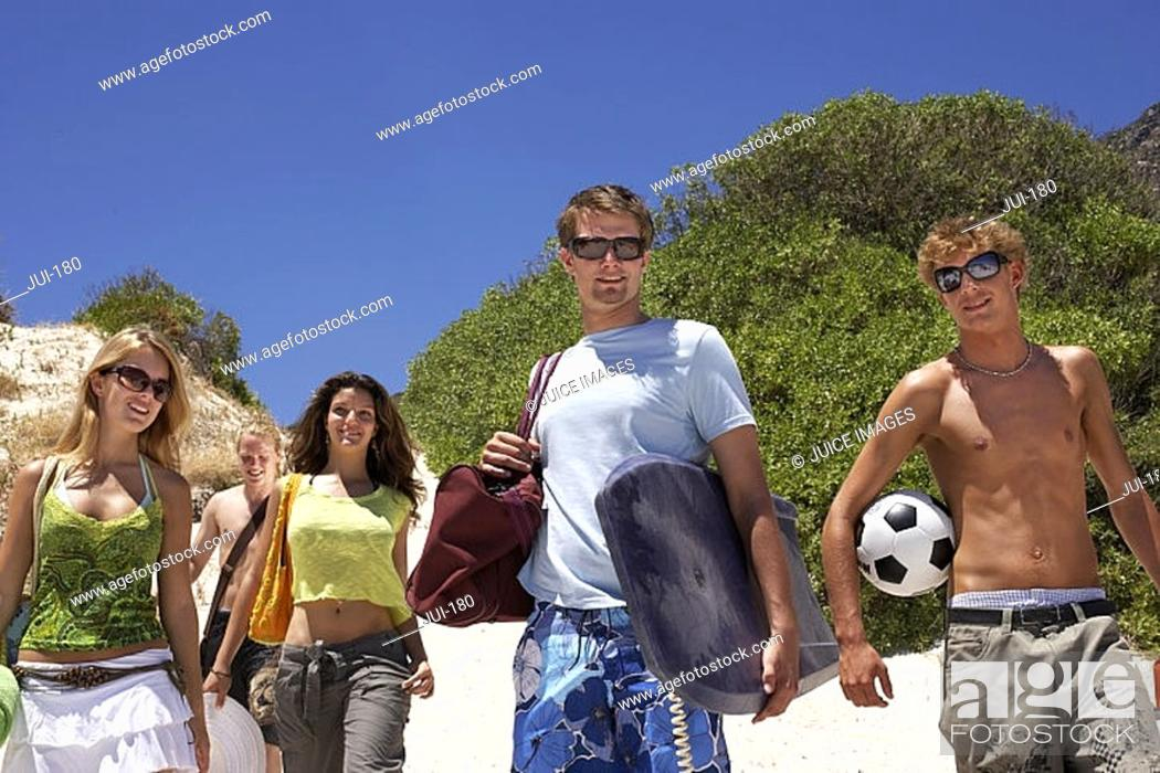 Stock Photo: Teenagers 17-19 standing on beach, carrying bodyboard, soccer ball and bags, smiling, portrait.
