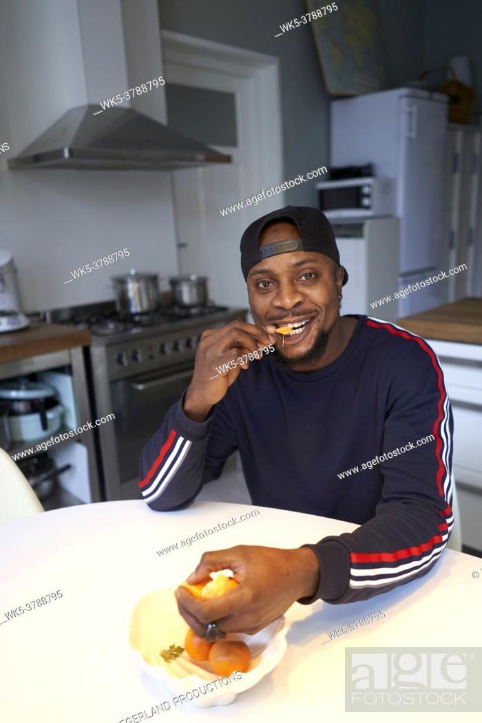 Stock Photo: African man eating orange in kitchen.
