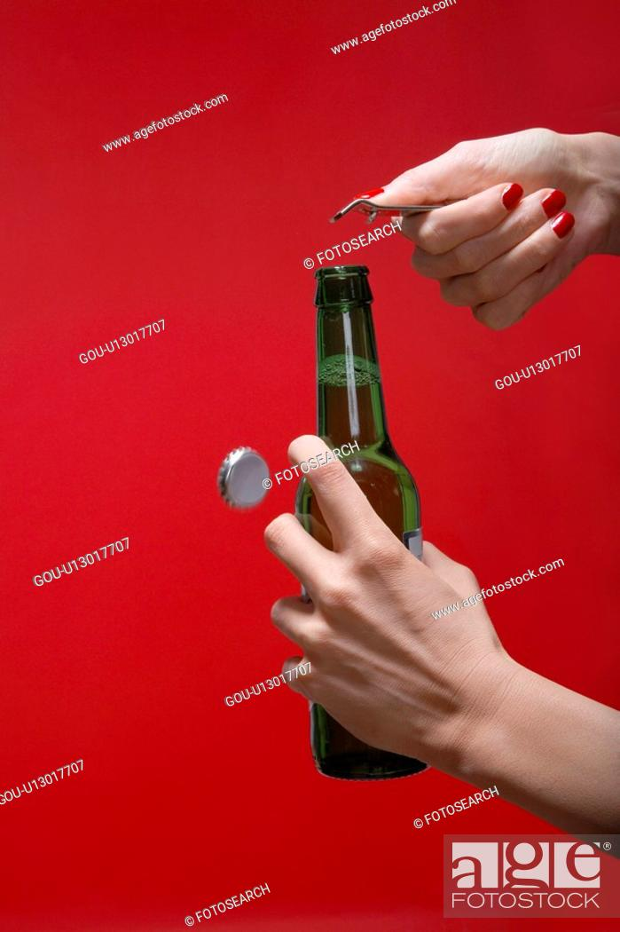 Stock Photo: Young woman's hands opening bottle of beer (close-up).