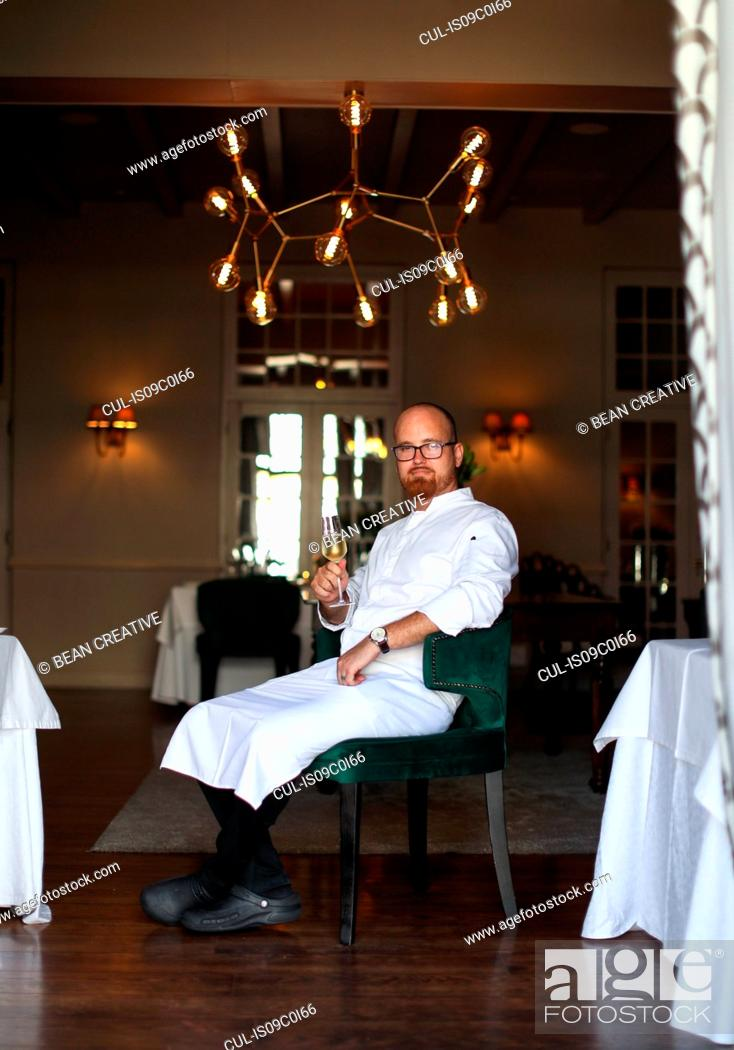 Stock Photo: Portrait of chef with glass of wine in luxury restaurant.